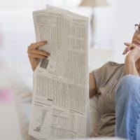 Woman reading newspaper in livingroom